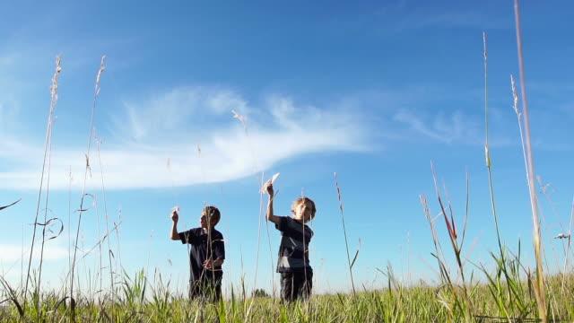 vídeos y material grabado en eventos de stock de dos niños volando papel aviones - avión de papel