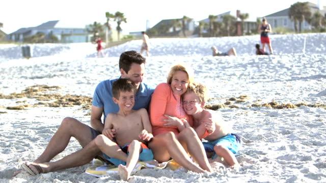 Zwei jungen bekommen Umarmung von Eltern am Strand