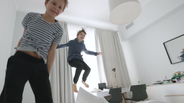 two boys having fun jumping on beds - zoom in stock videos & royalty-free footage