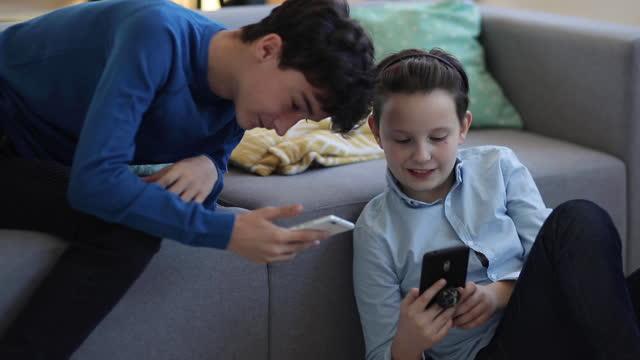 stockvideo's en b-roll-footage met twee jongens die pret hebben gebruikend sociale media terwijl zij uit thuis hangen - tienerjongens