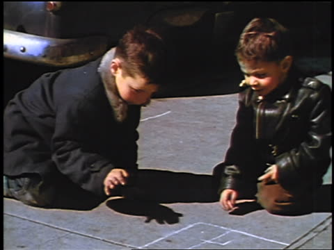 vídeos y material grabado en eventos de stock de 1957 two boys in coats drawing with chalk on sidewalk / feature - 1957