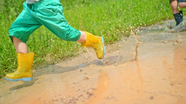 slo mo two boys in rain boots running across a muddy puddle in sunshine - wellington boot stock videos & royalty-free footage