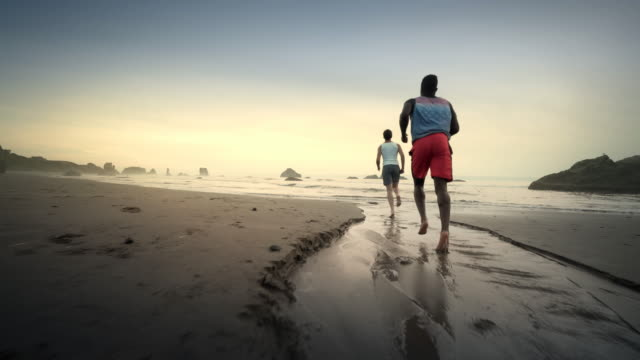 two boys jogging on beach at sunset, bandon oregon - the human body stock-videos und b-roll-filmmaterial