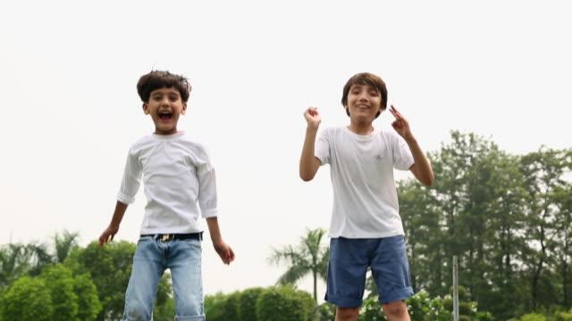 vídeos de stock e filmes b-roll de two boys jumping on the trampoline - trampolim equipamento desportivo