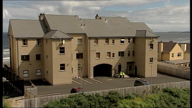 stockvideo's en b-roll-footage met two boys killed by carbon monoxide poisoning in castlerock holiday flat castlerock ext gvs of beach and rocks gv block of apartments apartments seen... - carbon monoxide