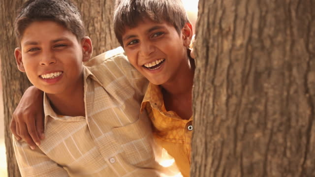 two boys laughing, faridabad, haryana, india - hugging tree stock videos & royalty-free footage