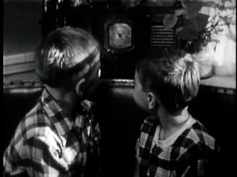 vidéos et rushes de b/w ms two boys listening to radio then turn around and laugh / los angeles, california, usa - écouter