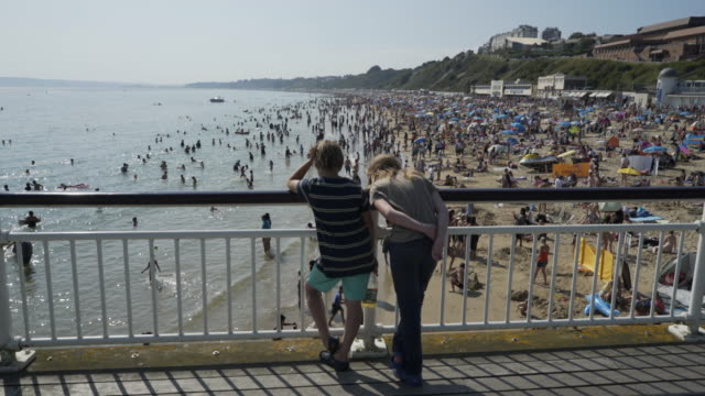 Two boys looking at the crowds of people on the beach.