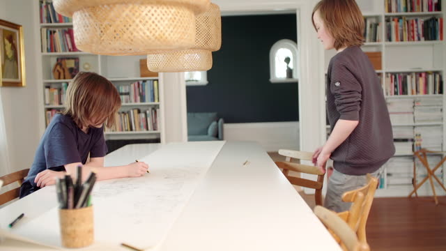 Two boys making drawing on a large piece of paper