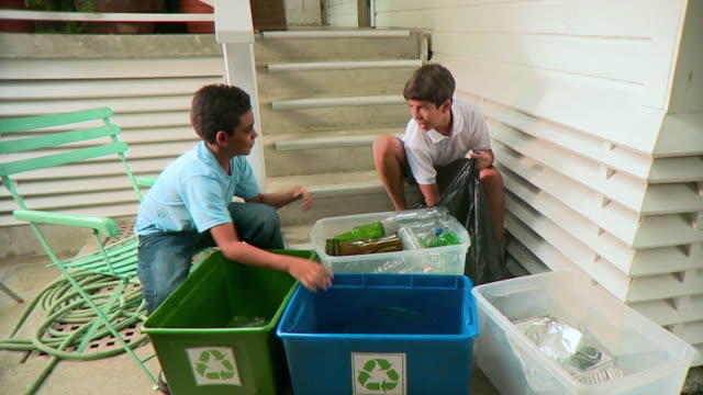 MS Two boys (9-12) organizing bottles into recycle bins, Panama City, Panama