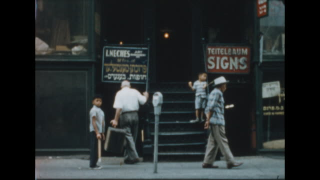 two boys play with balls on the ends of strings on the stoop in new york's lower east side advertisements for leeches and teitelbaum signs cus of ham... - lower east side bildbanksvideor och videomaterial från bakom kulisserna