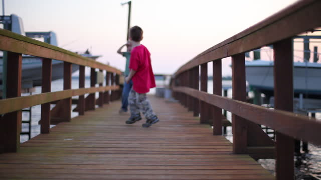 Two boys playfully run up and down an ocean dock acting like monsters.