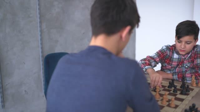 チェスのゲームをする2人の少年 - 余暇 ゲームナイト点の映像素材/bロール