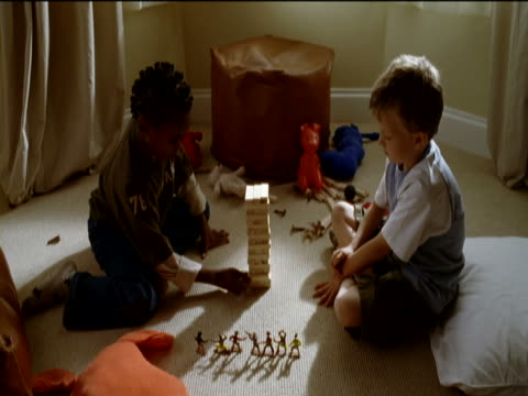 vídeos de stock, filmes e b-roll de two boys playing a game with toy blocks and then knocking them over, in a living room - almofada