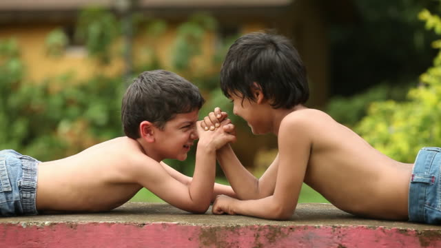two boys playing arm wrestling on the ledge of a park  - nackter oberkörper stock-videos und b-roll-filmmaterial