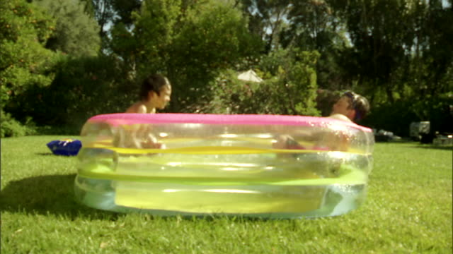 vidéos et rushes de ms, two boys (6-7) playing in inflatable pool in garden - pataugeoire