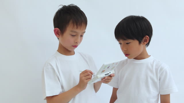 ms two boys (6-8) playing on handheld video game / shibuya, tokyo, japan - handheld video game stock videos & royalty-free footage