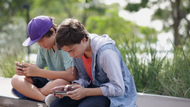 vidéos et rushes de ms two boys playing on their phones in a park. - amitié masculine