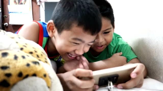 スマートフォンを再生する2人の少年 - ゲーム点の映像素材/bロール