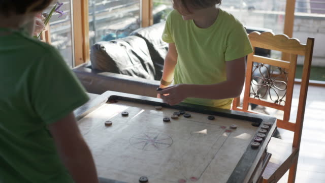 two boys playing the traditional asian game of game of carrom - carrom stock videos & royalty-free footage
