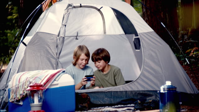 MS Two boys (10-11) playing video game in tent / Lynnwood, Washington State, USA