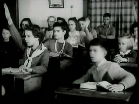 two boys playing w/ pegs. adult reading w/ children. grade school: history class boy answering question young girl & boy at desk. children standing... - amerikanischer treueschwur stock-videos und b-roll-filmmaterial