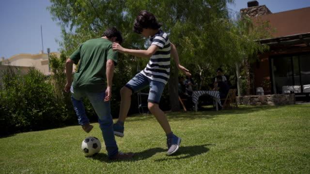 zwei jungs spielen mit einem fußball in ihrem hof - geschwister stock-videos und b-roll-filmmaterial