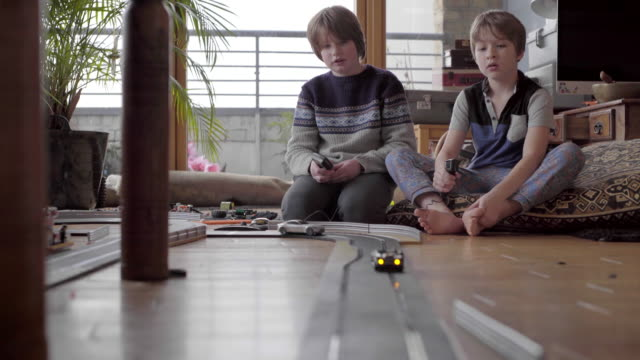 vidéos et rushes de two boys playing with slot cars on the floor at home. - children only