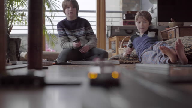 Two boys Playing with slot cars on the floor at home.