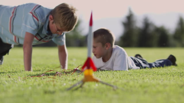 ws r/f two boys (6-7, 12-13) playing with toy rocket in park / orem, utah, usa - rakete stock-videos und b-roll-filmmaterial