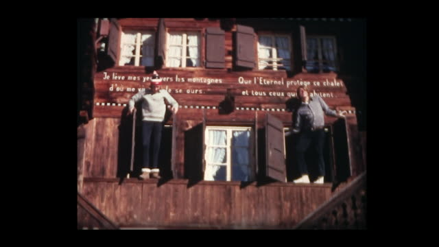 1971 two boys pop in and out of chalet windows - chalet stock videos & royalty-free footage