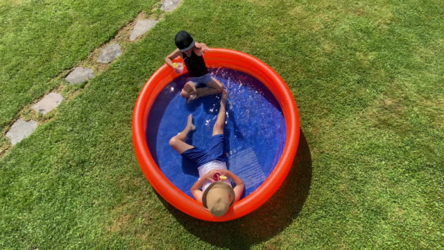 two boys relaxing in children's pool - 8 9 anni video stock e b–roll