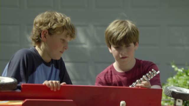 vídeos y material grabado en eventos de stock de cu shaky zo two boys (10-11) repairing toy car in driveway, encino, california, usa - camino de entrada