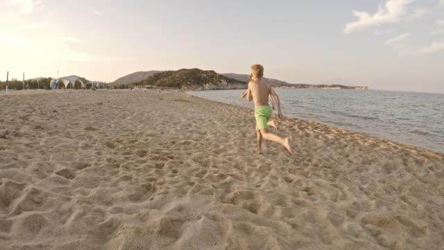 Zwei jungen laufen am Strand entlang am Meer