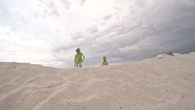 vidéos et rushes de deux garçons courir et sauter sur une dune de sable - 8 9 ans