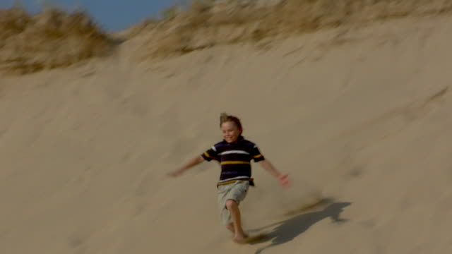 ms, ts, two boys (8-9, 10-11) running down sand dune,  provincetown, cape cod, massachusetts, usa - sand dune stock videos & royalty-free footage