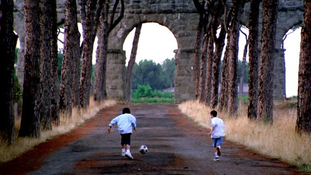 rear view two boys running + kicking soccer ball on road towards aqueduct arch / italy - italian culture stock-videos und b-roll-filmmaterial