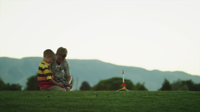 ws two boys (6-13) setting up toy rocket for launch on field / orem, utah, usa - orem utah stock videos & royalty-free footage