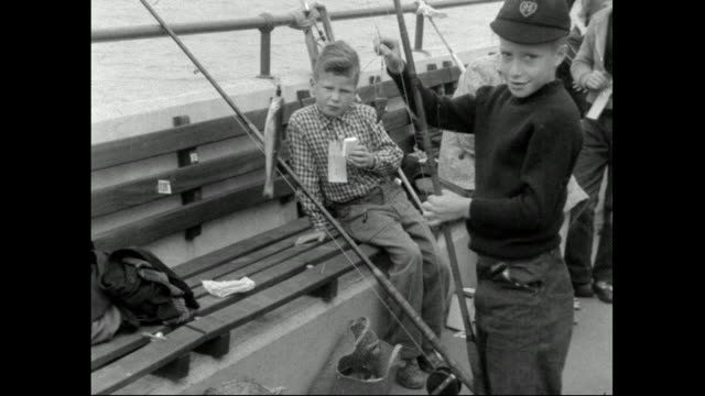 two boys show off prized fishing catches to cam; 1958 - fishing stock videos & royalty-free footage
