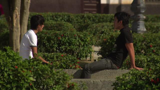 """two boys sit and relax on stone wall, plaza de la armas, chachapoyas, peru [perãº]"" - stone wall stock videos and b-roll footage"