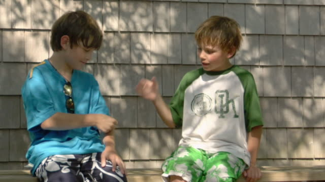 ms, two boys (8-9, 10-11) sitting on porch bench and playing rock paper scissors, truro, caped cod, massachusetts, usa - emotion stock videos & royalty-free footage