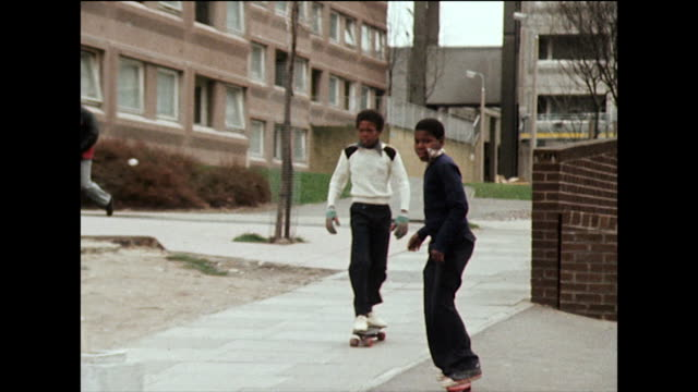 two boys skateboard on pavement in housing estate; 1980 - less than 10 seconds stock videos & royalty-free footage