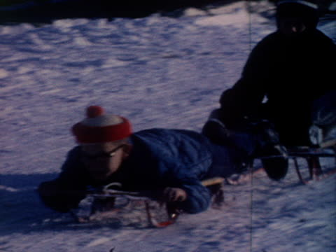 two boys sled downhill together. - sledge stock videos & royalty-free footage