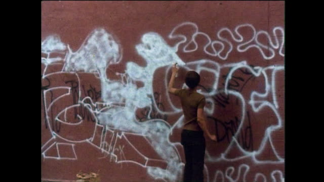 two boys spray paint a wall with graffiti in new york; 1976 - bbc archive stock-videos und b-roll-filmmaterial