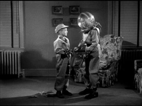 Two boys standing in living room dressed in spacesuits taller boy in round plastic helmet placing shoulder resting longer helmet on younger shorter...