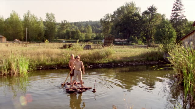 two boys standing on small wooden raft in middle of pond / one boy losing balance and jumping into water - losing virginity stock videos & royalty-free footage