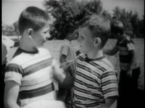b/w ms two boys standing with arms around each other while children shake hands behind them / usa - brother stock videos & royalty-free footage