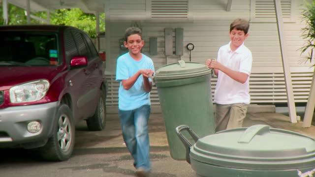ms two boys (9-12) take out garbage bins onto driveway, panama city, panama - chores stock videos & royalty-free footage