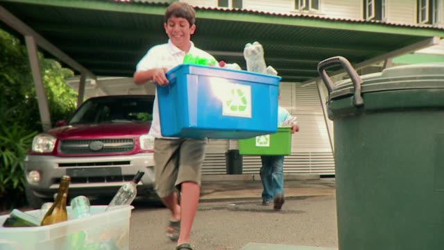 MS Two boys (9-12) take out recycle bins onto driveway, Panama City, Panama