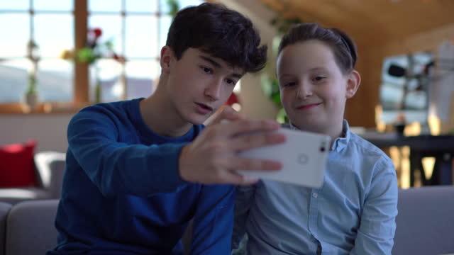 stockvideo's en b-roll-footage met twee jongens die een selfie nemen terwijl zij uit thuis hangen - tienerjongens
